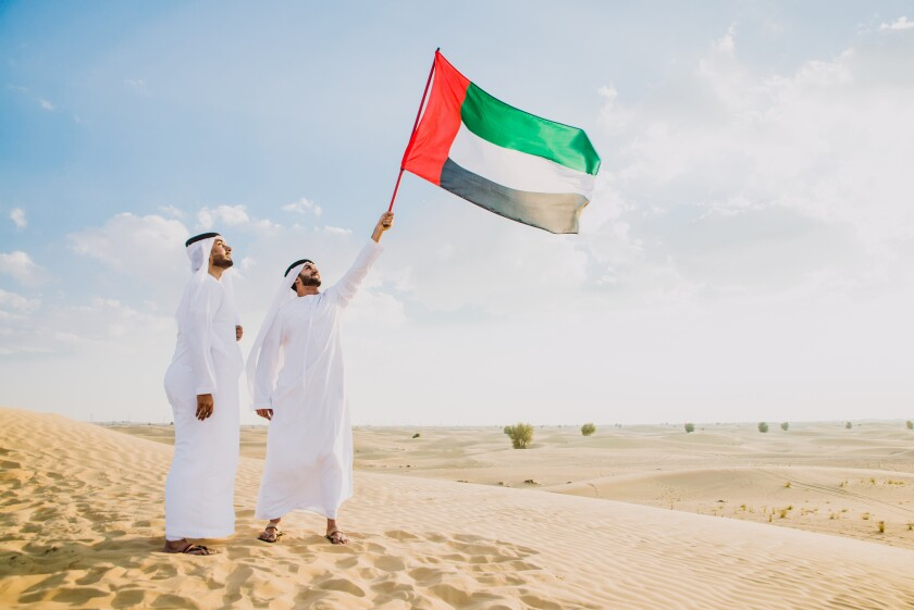 Man with white traditional kandura from uae praying in the desert on the carpet
