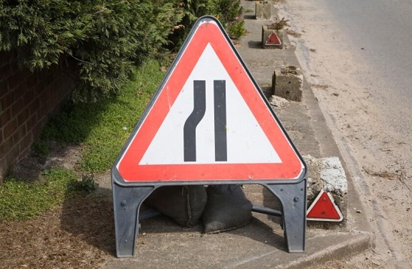 Red triangular sign warning of road narrowing ahead, UK
